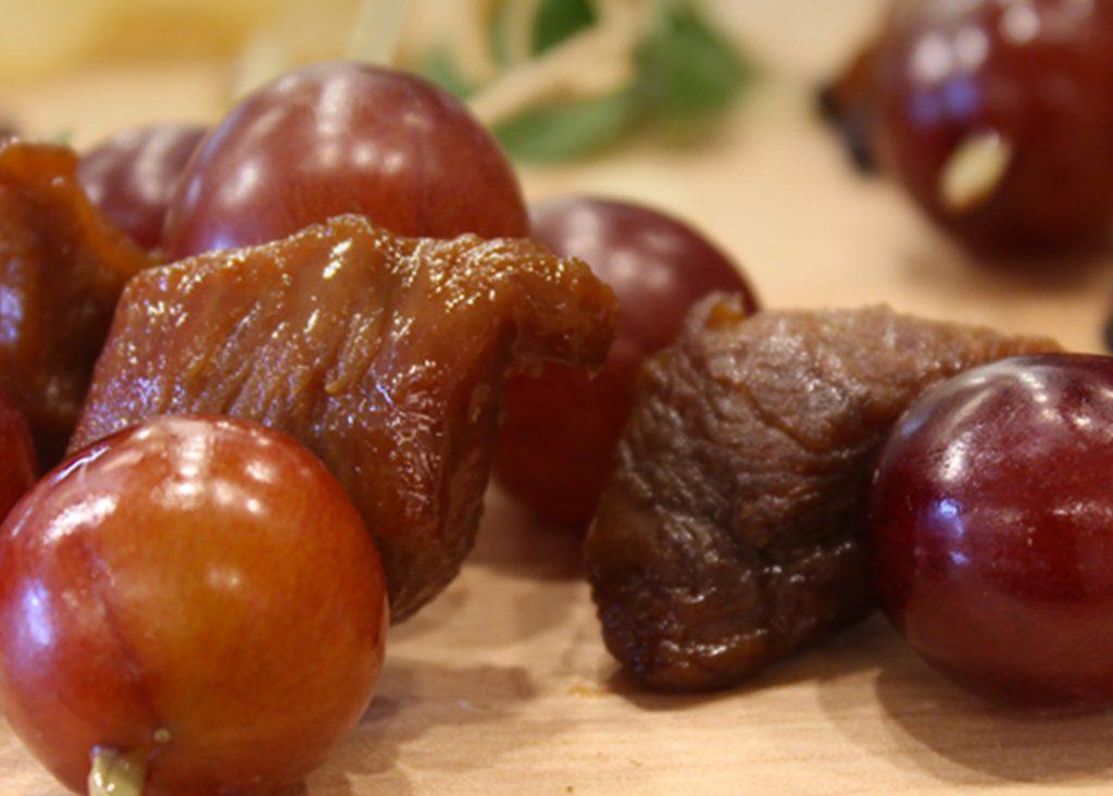 Hors-d'œuvre de brochettes de poitrine de canard en cubes laqué à l'orange et aux raisins